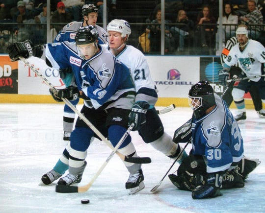 BC Icemen's Patrice Robitaille battles for control of the puck in front of goalie Erasmo Saltarelli during a game in 1999.