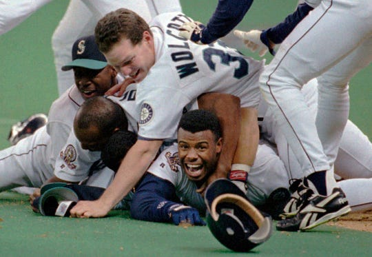 Seattle Mariners' Ken Griffey Jr. smiles from beneath a pile of teammates who mobbed him after he scored the winning run in the bottom of the 11th inning of a baseball game against the New York Yankees in 1995. The Mariners are the only baseball franchise never to advance to the Fall Classic.