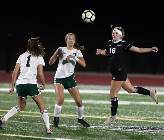Klahowya's Tori Peters (16) goes up for a header as Port Angeles's Bailee Larson (1) and Hannah Reetz (3) look on during their game on Tuesday, October 15, 2019.