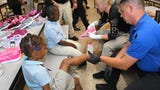 The Rockledge Kiwanis Club gives free new shoes out at Emma Jewel Academy Charter School, with help from Cocoa Police Dept.