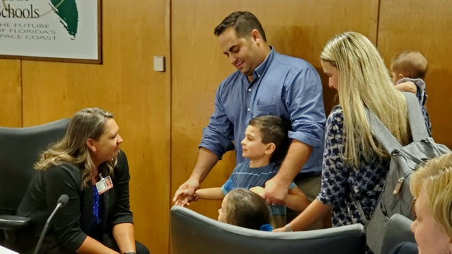 School Board member Misty Belford meets with the Pogars after Tuesday's board meeting.
