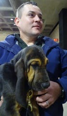 Bucyrus police Officer Amos Wolfe holds his new K9 partner, Ellie, a bloodhound, shortly before the puppy was introduced at a City Council meeting on Tuesday evening.