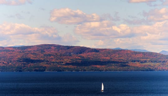 The white sails of a sloop on Lake Champlain stands in contrast to the Adirondacks bathed in fall colors seen from the Vermont side.