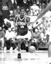 Eddie Benton dribbles the ball up the floor during a game for the University of Vermont men's basketball team.