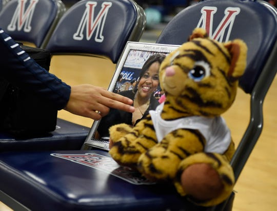 A Carroll volleyball players touches a photo of Stacy Selby before the game against Veterans Memorial, Tuesday, Oct. 15, 2019, at Veterans Memorial. Selby died Thursday night.