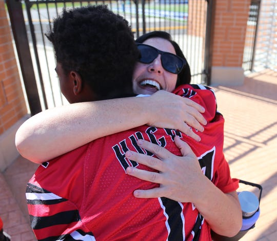 Dana Gendreau hugs a Hughes football player as he gets off the bus before the team's game on Saturday, Oct. 6, 2019.