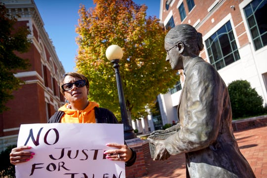 Lisa Lebron holds her sign for passing drivers to see while standing next to a statue in downtown Clarksville tributing to one of the first female documentary photographers in Clarksville at Montgomery County Court in Clarksville, Tenn., on Wednesday, Oct. 16, 2019.