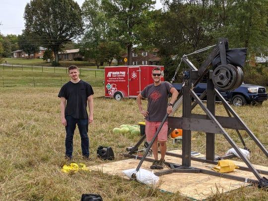APSU student Killian Prue (black shirt) and APSU physics lab manager Bryan Gaither (sunglasses) stand before Austin Peay's new trebuchet.