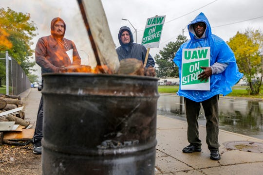 "UAW autoworkers Davor Janceski, 41, of Macomb; Edward LeBlanc 48, of Lincoln Park and Martin Jackson, 68, of Detroit  keep warm near a burn barrel while they strike in the rain in front of the General Motors Detroit-Hamtramck assembly plant in Hamtramck, Mich. on Wednesday, Oct. 16, 2019. General Motors and the UAW reached a proposed tentative agreement on a new contract Wednesday, the 31st day of a nationwide strike. ""I have faith in our leadership downtown UAW, no matter whats happening,"" says Strike Captain LeBlanc. ""As of right now we are setting a precedent for the next ten years and everybody is watching."""