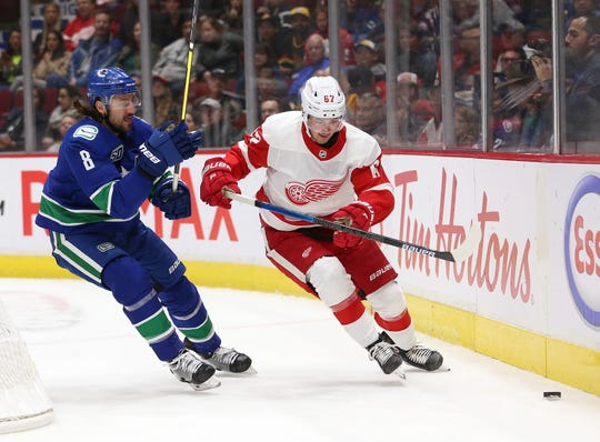 The Canucks' Christopher Tanev vies for the puck with Red Wings forward Taro Hirose during the second period of the Wings' 5-1 loss on Tuesday, Oct. 15, 2019, in Vancouver, British Columbia.
