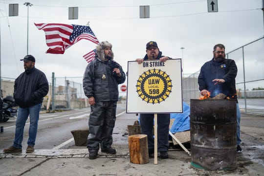 Flint Assembly electrician Mike Perez (center left) of Saginaw and (center rightly) Flint Assembly Electrician Alex Rodriguez of Detroit talk while standing on strike at the north gate of General Motors Flint Assembly on Wednesday, October 16, 2019.