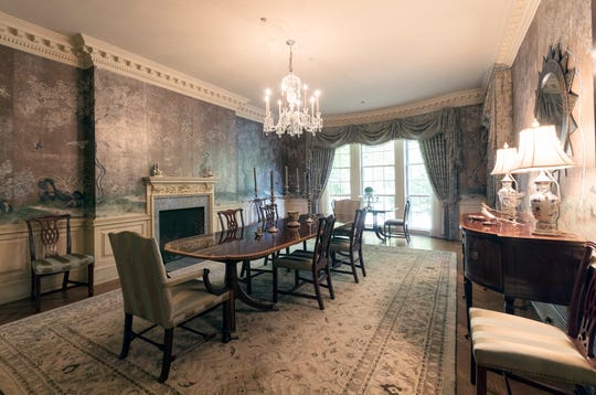 The long formal dining room is bowed at the far end with deep molding and wainscot. The silver wall covering is not paper, but hand-painted silk -- Gracie brand -- which often stays with a house through multiple owners.