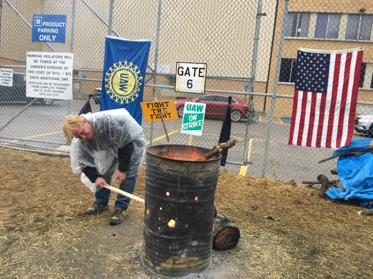 Michael Lintz, 46, a material driver from Richville stokes the fire on the strike line at the Flint Assembly Plant on Wednesday.