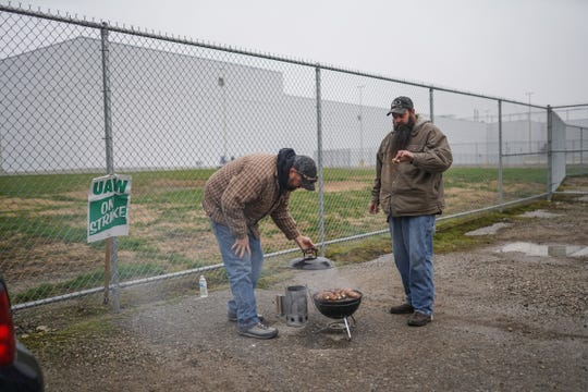 Flint Assembly material handler Martin Gunther and material driver Jesse Bayne check on their venison blackstrap jalapeño poppers as they were stand outside of General Motors Flint Assembly in Flint on Wednesday, October 16, 2019 while on strike.