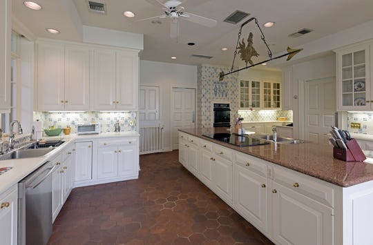 The large kitchen has a floor of terra cotta and trim of blue and white tile. Over the double oven the tile has a fish design.