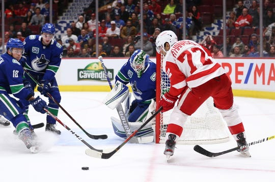 Canucks goalie Thatcher Demko makes a save against Red Wings forward Andreas Athanasiou during the first period of the Wings' 5-1 loss on Tuesday, Oct. 15, 2019, in Vancouver, British Columbia.