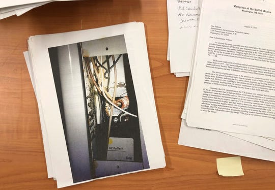 In this Feb. 5, 2019, photo, documents and an image of an old fluorescent light ballast sit on a table at the U.S. Environmental Protection Agency Region 2 headquarters in New York.
