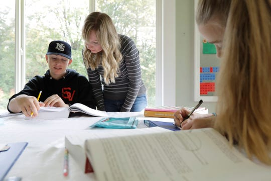 In this Oct. 9, 2019, photo, Donya Grant, center, works on a homeschool lesson with her son Kemper, 14, as her daughter Rowyn, 11, works at right, at their home in Monroe, Wash.