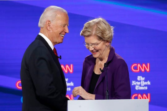 Democratic presidential candidate former Vice President Joe Biden, left, talks with Sen. Elizabeth Warren, D-Mass., during a Democratic presidential primary debate hosted by CNN/New York Times at Otterbein University, Tuesday, Oct. 15, 2019, in Westerville, Ohio.
