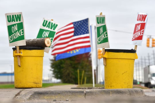 The U.S. and UAW flags blow in the wind in behind 'UAW On Strike' picket signs at the GM Warren Transmission Operations plant before picketers hear there may be a tentative deal to end the strike.