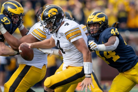 Michigan linebacker Cameron McGrone sacks Iowa quarterback Nate Stanley.