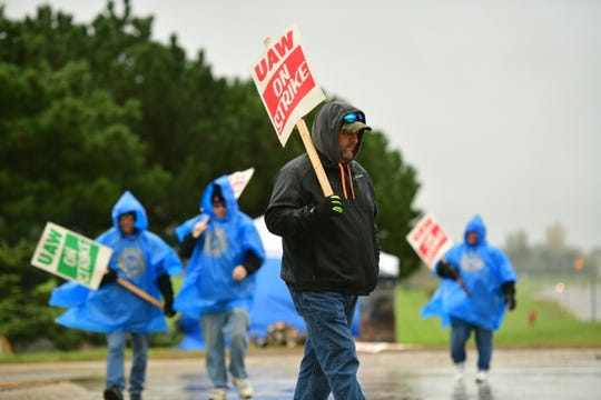 UAW local 5960 workers walk the line in the rain in front of the GM Lake Orion assembly plant in Lake Orion, Wednesday.