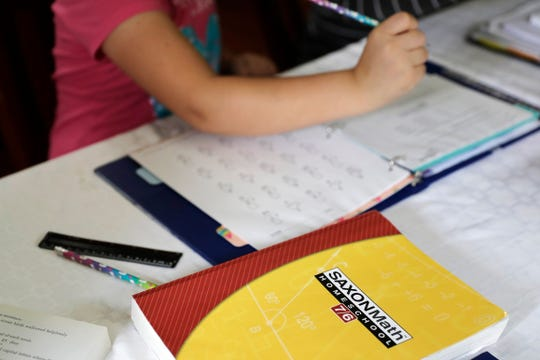In this Oct. 9, 2019 photo, a homeschool math textbook rests on the table where Mabry Grant, 8, works on a lesson with her mom, Donya Grant, at their home in Monroe, Wash.