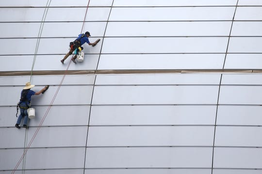 Workers clean the outside facade of State Farm Stadium in Glendale, Ariz.