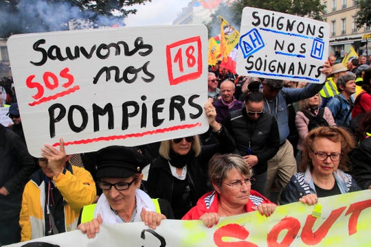 """Firemen and hospital staff demonstrate with posters reading """"Save our firefighters"""", left, and """"treat our caregivers"""" as they protest on wages, working conditions and pensions, Tuesday, Oct. 15, 2019 in Paris."""
