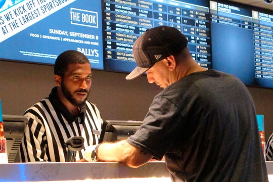 In this Sept. 5, 2019 photo, a gambler makes a sports bet at Bally's casino in Atlantic City N.J.