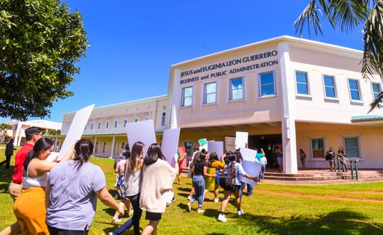Students and other supporters march into the Jesus and Eugenia Leon Guerrero Business and Public Administration building to express their opposition to a proposed increase in tuition rates being considered at the University of Guam on Wednesday, Oct 16, 2019.