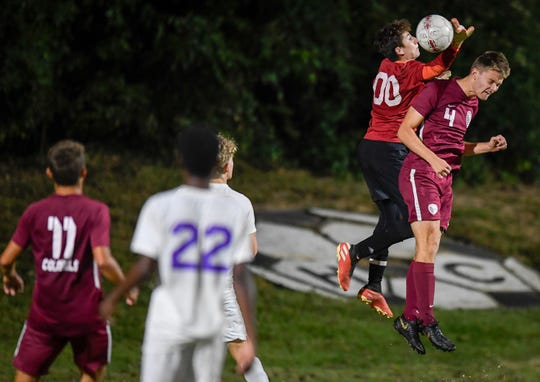 Henderson County's Lucas Butler (4) goes up with Lyon County goalie Cole Schroeder (00) to control a corner kick to score in the second period as the Henderson County Colonels play the Lyon County Lyons in a first round game of the Boys Second Region Soccer Tournament Tuesday evening at Henderson's Colonel Field, October 15, 2019.