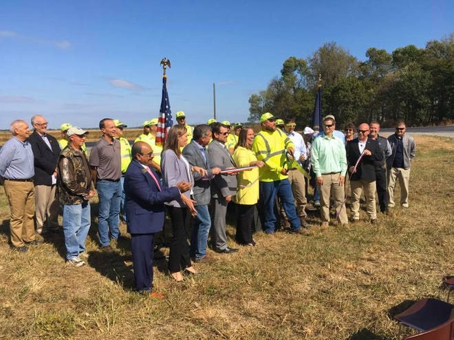 Government officials, highway workers and others gather to cut the ribbon on a $2 million U.S. 60-West improvement project.