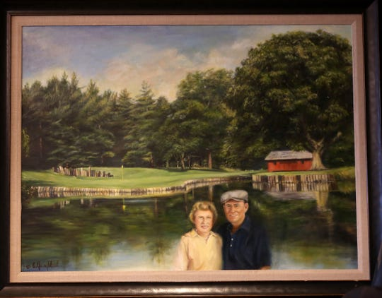 A painting portrays  Alice and Pete Dye at the sixth hole of Crooked Stick Golf Club.  The Dyes designed the course in Carmel, Indiana.