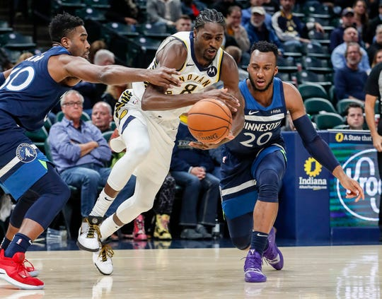 Indiana Pacers forward Justin Holiday (8) passes the ball against Minnesota Timberwolves guard Josh Okogie (20) during the second half against the Minnesota Timberwolves, Tuesday, Oct. 15, 2019, Bankers Life Fieldhouse, Indianapolis. Timberwolves defeat Pacers 119-111 in preseason finale.