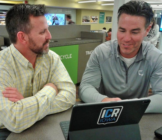 "Dave Brown (left) and Ryan Bell became friends after being paired in the Wingman Program of ICR Iowa, which matches active local volunteers with a newcomer in search of an ""insider"" view of their future community. Here they touch base in the University of Iowa main library."