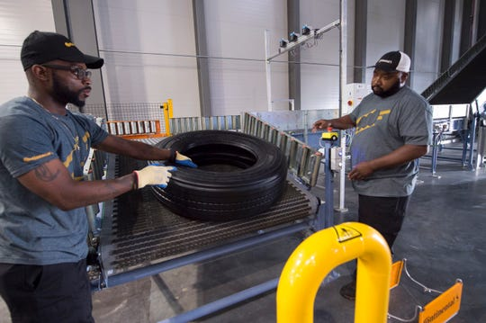 Continental Tire employees pull the first tire off the line during the plant's grand opening celebration Wednesday, Oct. 16, 2019. The plant, with 200 positions filled to date and an anticipated 2,500 jobs created by 2028,  will produce large truck and bus tires for the U.S. market. Production is set to begin in 2020.