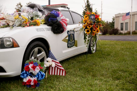 Tokens left behind from visitors cover an Indiana State Police cruiser parked outside the Lafayette ISP post to memorialize Trooper Peter Stephan, Tuesday, Oct. 15, 2019 in West Lafayette. Trooper Stephan died Friday night in a single-car crash.