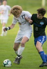 South Lyon's John Hull (17) and Walled Lake Western's Francisco Korn (8) battle for the soccer ball in a district semifinal at Brighton on Tuesday, Oct. 15, 2019.