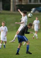 South Lyon's Cade White goes up for a header against Walled Lake Western's J.T. Groves in a district semifinal soccer game on Tuesday, Oct. 15, 2019 at Brighton.