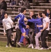 Matt Ampunan of Detroit Catholic Central celebrates his tie-breaking goal on a penalty kick in overtime against Howell on Tuesday, Oct. 15, 2019.