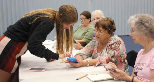 Presenter and Lely High School junior Ellie Poling confers about a smart phone technicality with Judy Daye.
