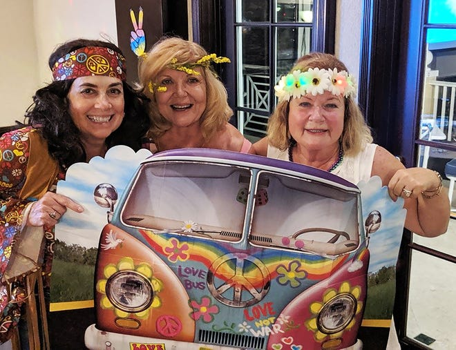 From left, Deb Devries, Kathleen Douglas and Angela Holt hop on a VW bus to get to the fun at the Marco island Yacht Club celebration of the 50th Anniversary of Woodstock.