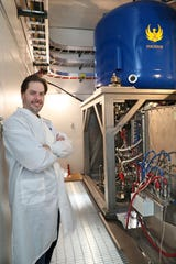 Shine Medical Technologies founder and CEO Greg Piefer stands next to the neutron generator at the company's demonstration plant. The neutron generator was made by  Phoenix, an affiliated company based in Monana that also was founded by Piefer.