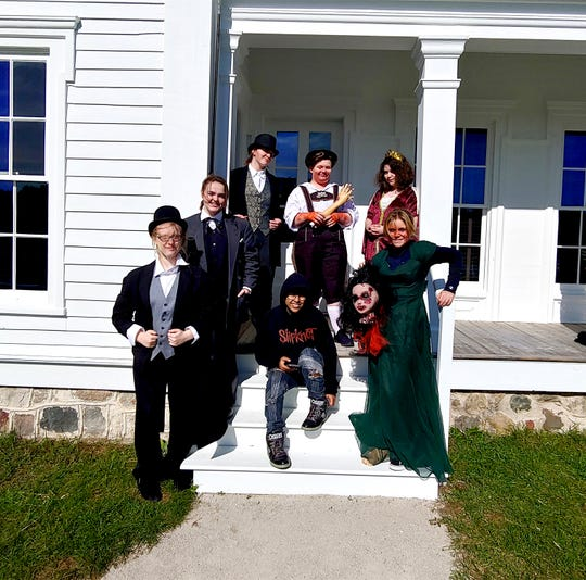 KM Perform students pose in front of the Grimm House at Old World Wisconsin for a daytime dress rehearsal. Pictured are (from left, front row)  Sarah Conner, Meghan Butenhoff, Cam Cooley, Ava Mastrocola, (back row) Ashley Bonestroo, Lauren Pavlet and Mae Weghorst.