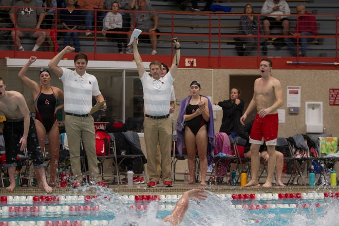 Ball State men's swimming and diving head coach J. Agnew (center), also the women's swimming and diving head coach for the Cardinals, celebrates.