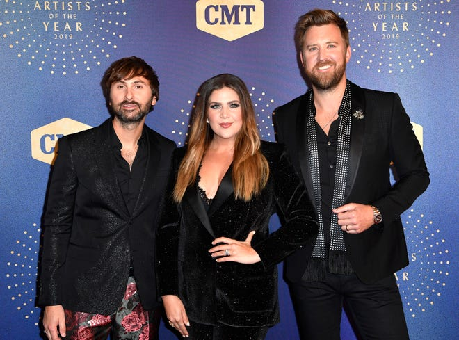 Dave Haywood, Hillary Scott and Charles Kelley of Lady A walk the red carpet before the CMT Artists of the Year show at the Schermerhorn Symphony Center in Nashville on Oct. 16, 2019.