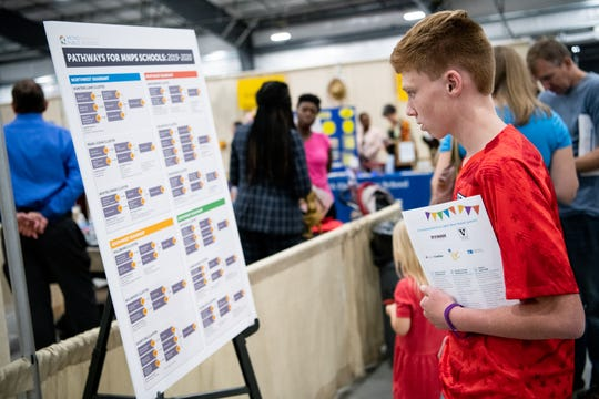 Alex Clanney, 13, looks at a post of the pathways for MNPS schools during the School Choice Festival at the Fairgrounds in Nashville, Tenn., Tuesday, Oct. 15, 2019.