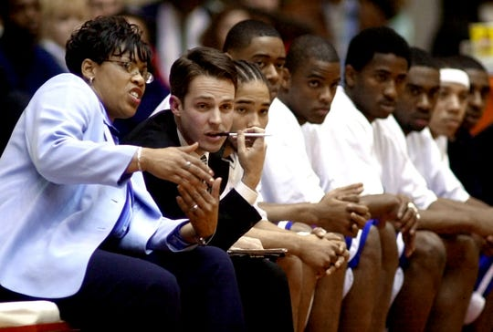 Tennessee State athletics director Teresa Phillips, left, talks with assistant coach Chris Graves as she coaches the men's basketball team during a game against Austin Peay on Feb. 13, 2003. Phillips was the first woman to coach a men's team in a Division I basketball game.