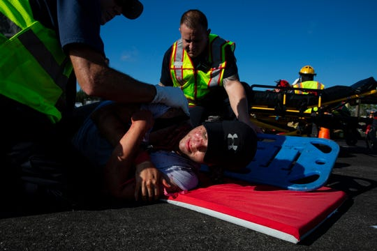 Emergency personnel roll Paloma Garnica onto a spinal board during a simulated mass casualty drill, Wednesday, Oct. 16, 2019, at the Naples Airport.